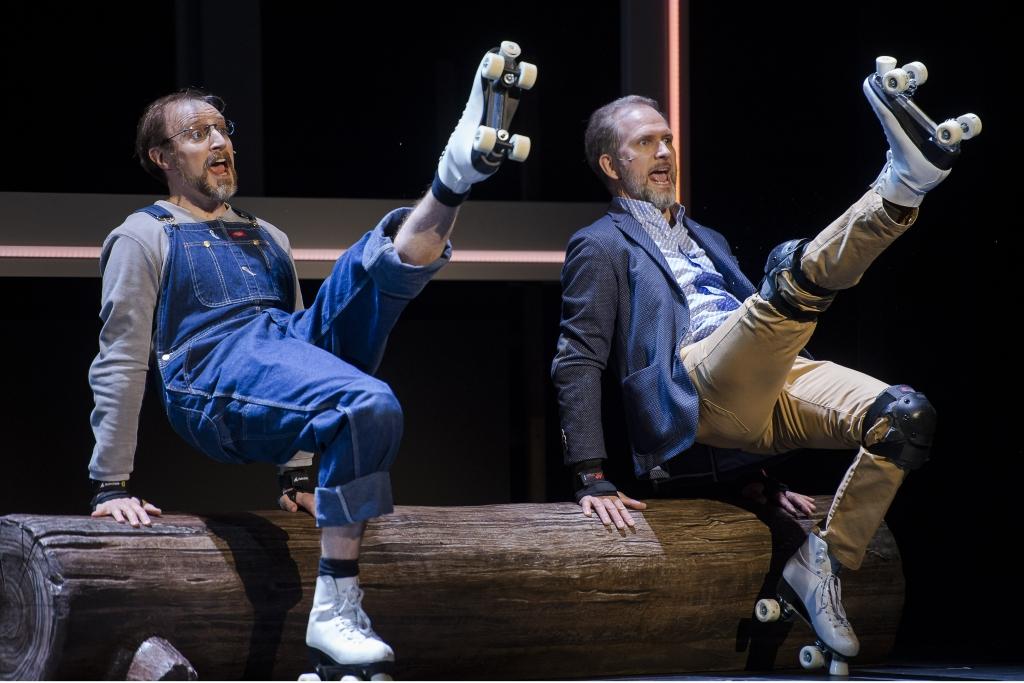 Ein Mann mit Latzhose und Brille und ein Mann in Sakko und beiger Jeans sitzen auf einem Baumstamm. Sie lehnen sich zurück und strecken jeweils ein Bein nach oben. An ihren Füßen befinden sich weiße Rollschuhe.