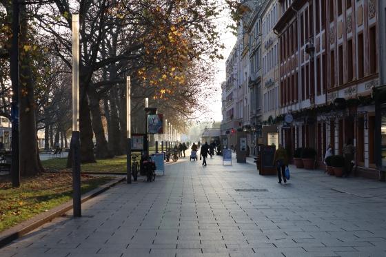 Die Dresdner Hauptstraße. Links sind Laubbäume mit orange-goldenen Blättern. In der Mitte mehrere Silhouetten von Menschen, die sich im Gegenlicht auf der mit Gewehgplatten ausgelegten Fußgängerzone fortbewegen. Rechts Fassaden in Rot- und Orangetönen.