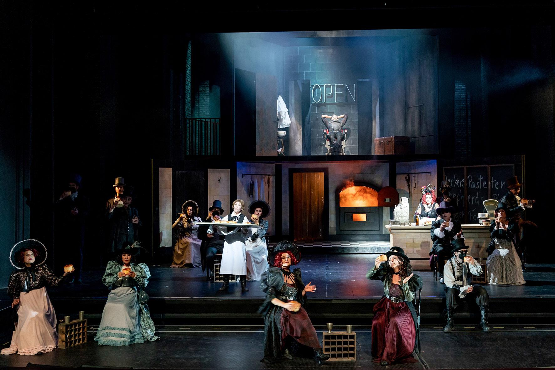 Gesamtansicht des dunkel gehaltenen Bühnenbildes. Im Vordergrund verteilt sitzende Mitglieder des Chores in Gothic-Kleidung. Weiter hinten der Bühnenaufbau: Im Erdgeschoss eine Theke, an der Mrs. Lovett mit roten Haaren steht. Dahinter der glühende Ofen. Im Obergeschoss der Barbiersalon. Sweeney Todd sitzt im Barbier-Stuhl.